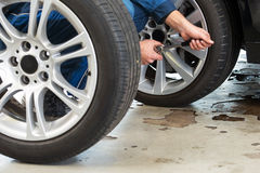 Mechanic changing tires. A mechanic tightening the wheel nuts on an alloy light weight rim afhter having exchanged summer tires for winter tires Stock Image