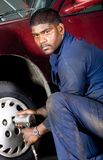 Mechanic changing tyre Royalty Free Stock Image