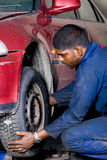 Mechanic changing tyre Royalty Free Stock Images