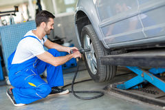 Mechanic changing tyre on car with air wrench Stock Image