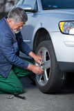Mechanic changing a wheel Stock Image