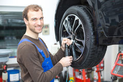 Mechanic changing wheels on a car on hydraulic ramp Stock Images
