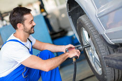 Mechanic changing wheel on car Stock Photo