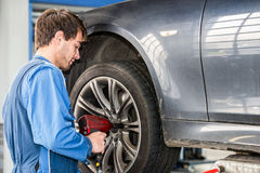 Mechanic Changing Wheel On Car With Pneumatic Wrench Stock Photography