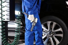 Mechanic changing wheel in car service. Closeup Stock Photography