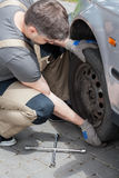 Mechanic changing wheel in car Royalty Free Stock Photography