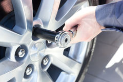 Mechanic changing wheel on car. With a wrench Stock Photos
