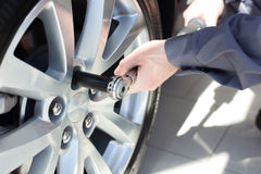 Mechanic changing wheel on car. With a wrench Stock Photo