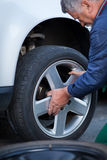 Mechanic changing a wheel of a modern car Stock Images