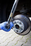 Mechanic changing a wheel. Of a modern car Royalty Free Stock Image