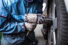 Mechanic changing a wheel of a modern car Royalty Free Stock Images