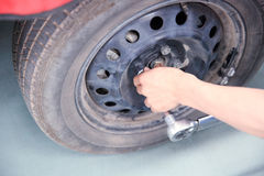 Mechanic changing wheels Royalty Free Stock Images
