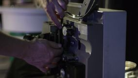 The mechanic charges the film in an old film projector. Close-up of a reel with a film. Operation of the film projector mechanism stock footage