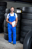 Mechanic checing clipboard car tires. In tire store Stock Images