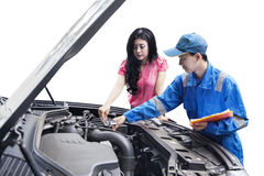 Mechanic checking the car machine with the owner Royalty Free Stock Photos