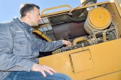 Mechanic checking cranes engine Royalty Free Stock Photography