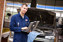 Mechanic: Checking Diagnostics on Laptop. Extensive series of a woman who has taken her car to the auto service garage, and the mechanic who works on her truck stock photography