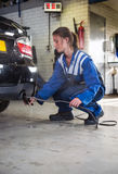 Mechanic checking diesel exhaust emission rates. Young, female mechanic, checking the disel exhaust emission rates during a periodic check, using diagnostics Royalty Free Stock Photography