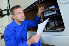 Mechanic checking electrics on campervan. Mechanic royalty free stock photo