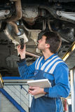 Mechanic checking an exhaust for gas leaks stock photos