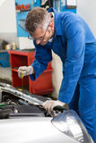 Mechanic checking the oil of car Stock Images