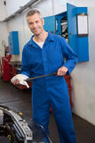 Mechanic checking the oil of car Royalty Free Stock Photo