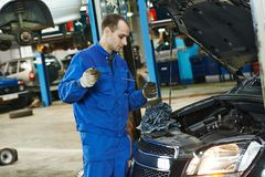 Mechanic checking oil level in automobile Royalty Free Stock Images