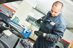 Mechanic checking oil level in automobile Stock Photos