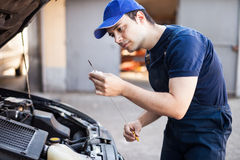 Mechanic checking the oil level. In a car engine royalty free stock image