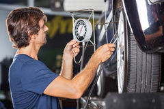 Mechanic Checking Pressure While Inflating Car Royalty Free Stock Images