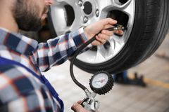 Mechanic checking tire pressure in service center. Closeup royalty free stock images