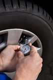 Mechanic checking tire pressure using gauge Royalty Free Stock Images
