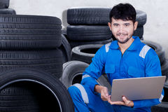 Mechanic is checking tires with a laptop. Image of young male mechanic is checking tires while holding laptop computer in the tire warehouse Royalty Free Stock Image