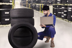 Mechanic checking the tires in store. Portrait of Arabian mechanic checking the tires while holding laptop in the tire store Royalty Free Stock Photo