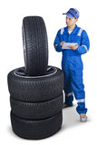 Mechanic checking tires with a tablet. Male mechanic with blue uniform, using a digital tablet to check the tires texture, isolated on white royalty free stock photography