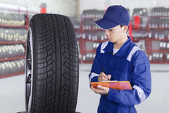 Mechanic checking tires in workshop Stock Photo
