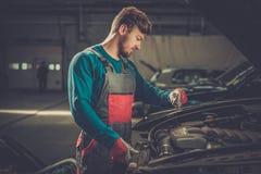 Mechanic checking under hood Stock Photo