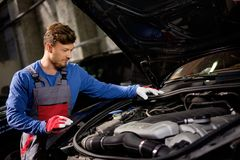 Mechanic checking under hood Stock Photos