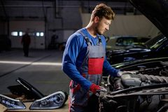 Mechanic checking under hood Royalty Free Stock Images