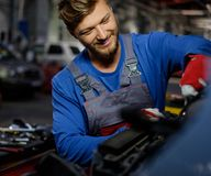 Mechanic checking under hood Royalty Free Stock Image