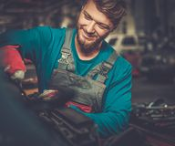 Mechanic checking under hood Royalty Free Stock Photos