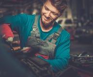 Mechanic checking under hood Royalty Free Stock Photos