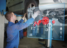 Mechanic checking wheel of a car helped by interface Stock Images