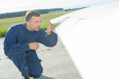 Mechanic checking wing tip aircraft Stock Photo