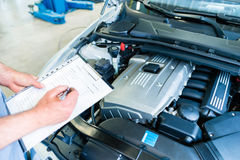 Mechanic with checklist in car workshop. Auto mechanic controlling  car with checklist in workshop Stock Photo