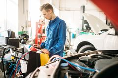 Mechanic checks air conditioning system in car royalty free stock photo