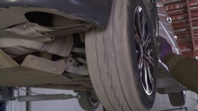 A mechanic checks car wheels.  stock video footage