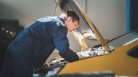 A mechanic checks the electrical in the hood of the yellow car- repairing in engine compartment Royalty Free Stock Image