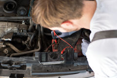 Mechanic checks electronics accumulator. With measuring equipment royalty free stock photos