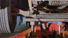Mechanic checks working capacity of wheel. Auto mechanic is under the bottom of truck. Professional worker checks the parts of truck from the down. Man views stock video footage